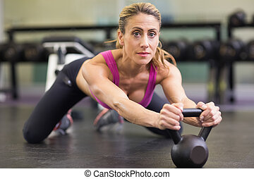 Serious woman lifting kettle bell