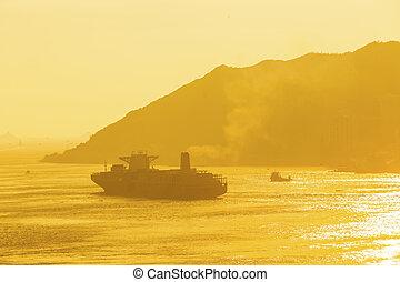 Cargo ship under sunset