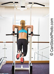 Rear view of fit woman doing crossfit fitness workout gym -...