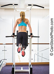 Fit woman doing crossfit fitness wo - Rear view of a young...