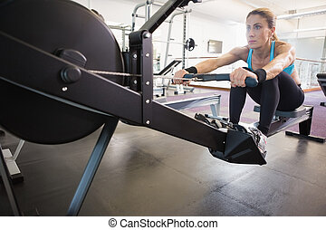 Woman working on fitness machine at gym - Full length of a...