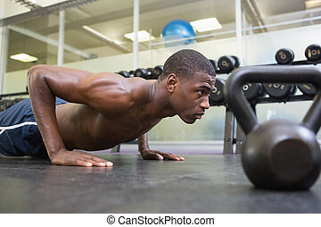 Shirtless muscular man doing push ups in gym - Side view of...