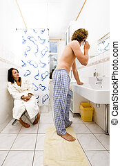 Sharing a bathroom - Young couple sharing a bathroom with a...