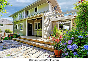 Cozy walkout deck with pergola and blooming flowers -...