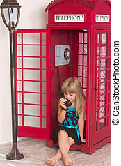 girl calling in red a phone - child girl calling in red in a...