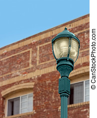 Vintage design electrical streetlamp with red brick building...