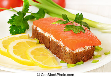 Sandwich with salmon, lemon slices and parsley