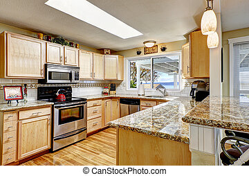 Bright kitchen with granite tops and skylight - Bright...