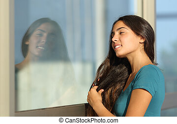 Flirty teen girl combing her hair using a window like a...
