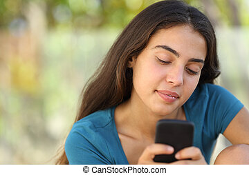 Pretty teenager girl texting in a smart phone - Pretty happy...