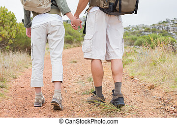 Hiking couple walking on mountain terrain - Rear view of...
