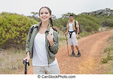 Hiking couple walking on mountain terrain - Portrait of...