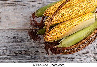 Fresh corn in basket on the wooden table