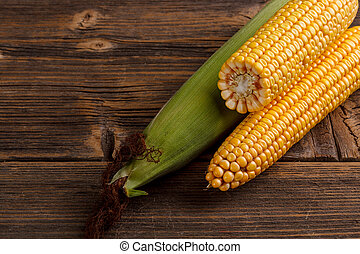 Fresh corn cobs on rustic wooden background