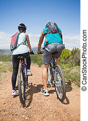 Athletic couple mountain biking - Full length rear view of...