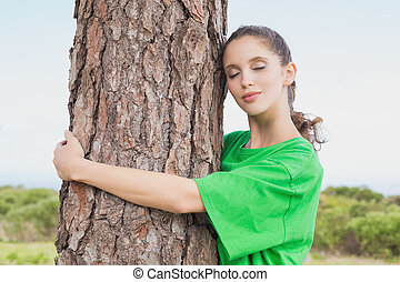 Female environmental activist hugging tree trunk - Side view...