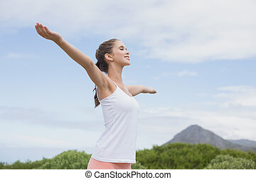 Beautiful woman with arms raised against sky