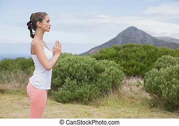 Woman with hands joined standing on countryside landscape -...