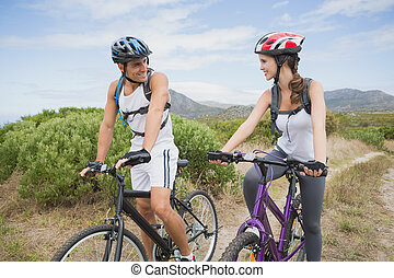 Athletic couple mountain biking - Full length of an athletic...