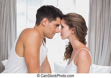 Romantic couple sitting in bed at home - Side view of...