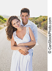 Loving couple standing on countryside road - Portrait of a...