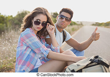 Couple hitchhiking on countryside road - Portrait of young...