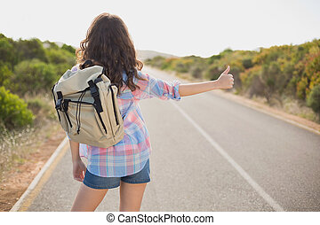 Woman hitchhiking on countryside road - Rear view of a young...