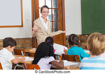Pretty teacher talking to the young pupils in classroom at...