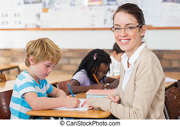 Pretty teacher helping pupil in classroom smiling at camera...