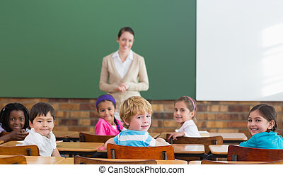 Cute pupils and teacher smiling at camera in classroom at...