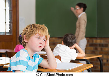 Cute pupil not paying attention in classroom at the...