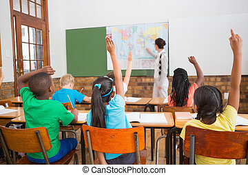 Teacher giving a geography lesson in classroom at the...
