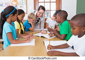 Teacher and pupils working at desk together