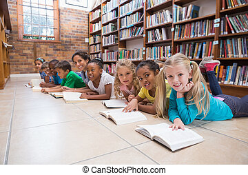 Cute pupils and teacher lying on floor in library at the...