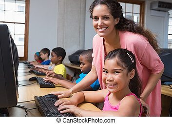 Cute pupils in computer class with teacher at the elementary...