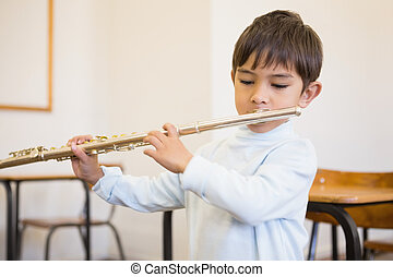 Cute pupil playing flute in classroom at the elementary...