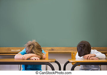 Sleepy pupils napping at desks in classroom at the...