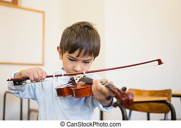 Cute pupil playing violin in classroom