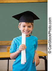 Cute pupil in mortar board smiling at camera in classroom at...