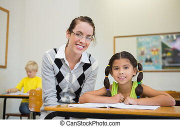 Pretty teacher helping pupil in classroom