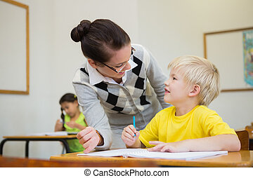 Pretty teacher helping pupil in classroom at the elementary...