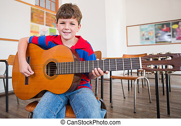 Cute pupil playing guitar in classroom at the elementary...