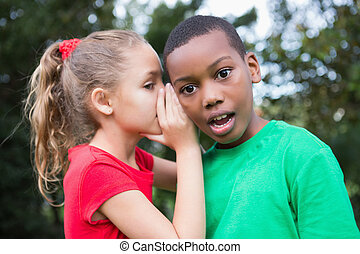 Cute children sharing gossip outside in the park