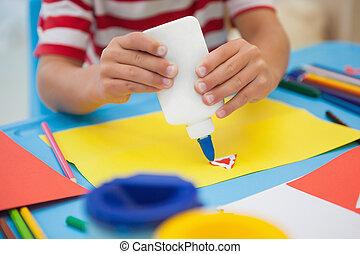 Little boy making art in classroom - Cute little boy making...