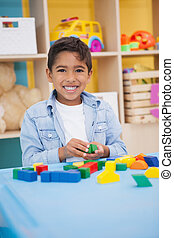 Cute little boy playing with building blocks at the nursery...