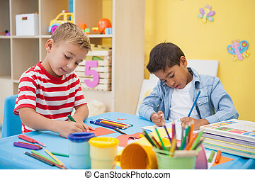 Cute little boys making art together in classroom at the...