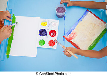 Cute little boys painting at table in classroom at the...