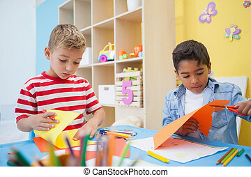 Cute little boys cutting paper shapes in classroom at the...