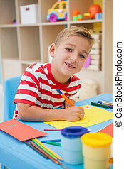 Cute little boy making art in classroom