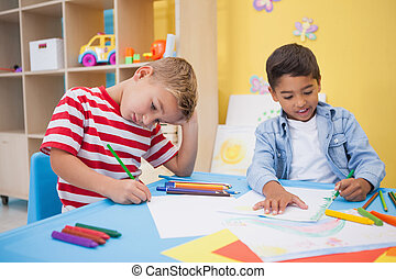 Cute little boys drawing at desk at the nursery school